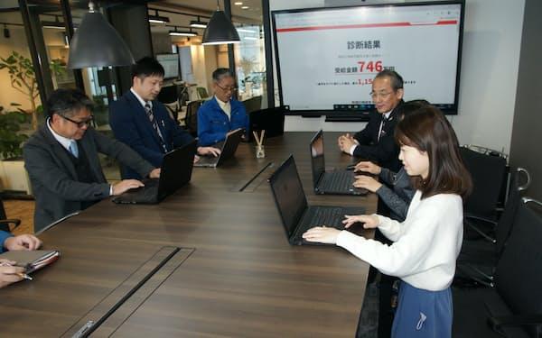 社内の会議はテーブルを上げて席を立つルールにして、短時間で済ませる(高知市の岡村文具本社)