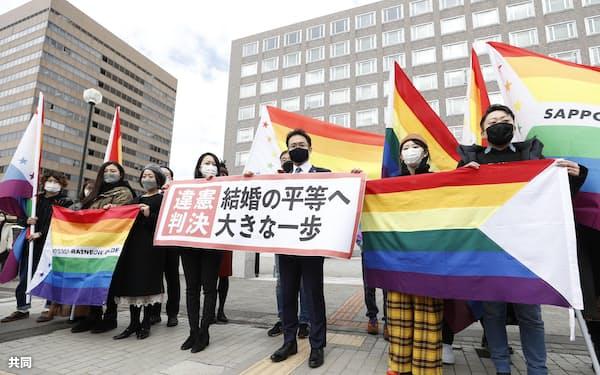 同性婚訴訟(そしょう)の判決後、「違憲判決」と書かれた紙をかかげる弁護士(べんごし)ら(17日、札幌市)=共同