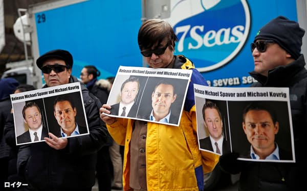 中国当局に拘束されたスパバ氏とコブリグ氏の解放を求める人たち=ロイター
