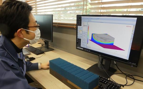体圧が介護用マットレスに与える影響を分析する研究員(タイカ宮加三事業所)