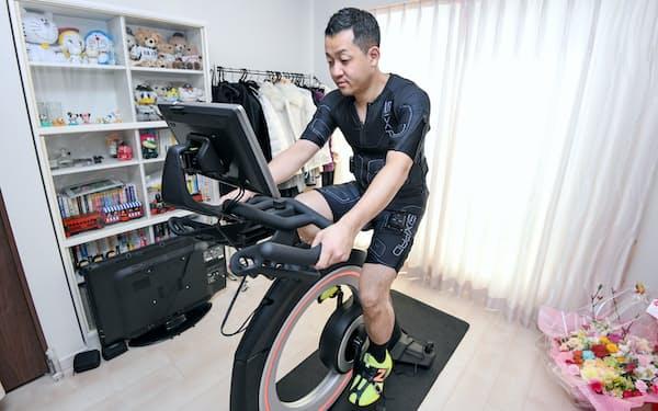電気刺激を与えるウエアを着て室内用バイクをこぐ目谷さん(3月3日、千葉県船橋市)