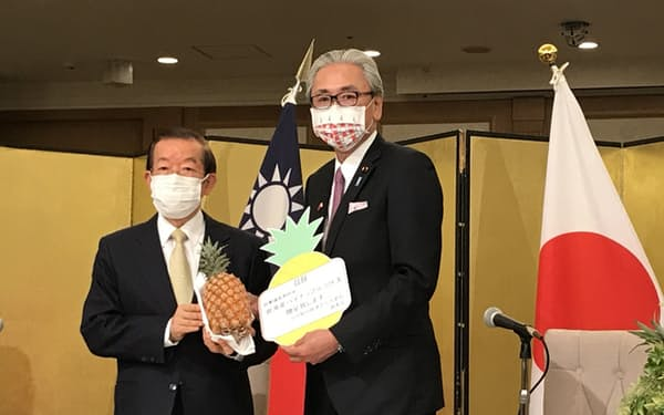 台北駐日経済文化代表処の謝長廷代表からパイナップルを受け取る古屋氏(22日、都内)
