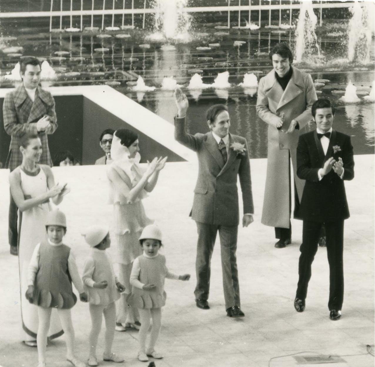 大阪万博のファッションショーであいさつするピエール・カルダン氏(1970年、中央で右手を挙げる人物)=高島屋史料館提供