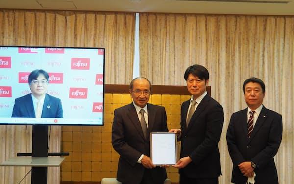 移住・ワーケーションに関する連携協定を結んだ富士通の時田社長㊧と大分県の広瀬知事(左から2人目、24日、大分県庁)