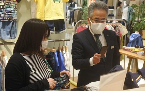 自宅にいる顧客にスマホを使って贈答用の子供服を案内する岩田屋三越の外商担当㊨(福岡市)