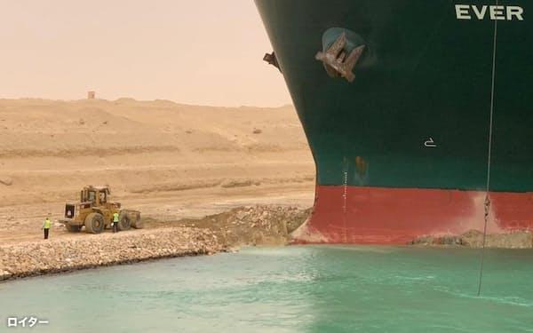24日、スエズ運河の座礁船復旧にあたる作業員=ロイター