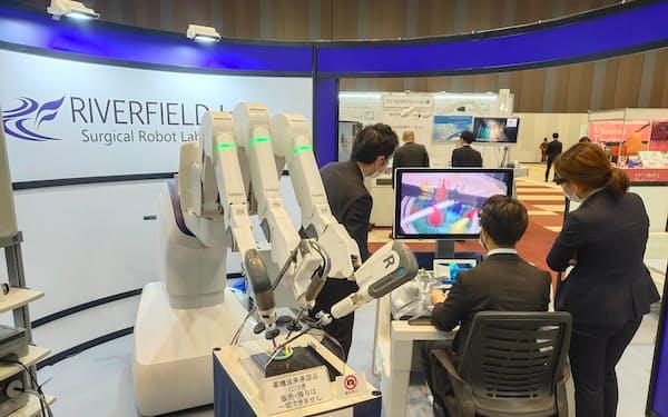 リバーフィールドのロボでは術者(右)の操作に従って3本のアームが動いて手術を行う