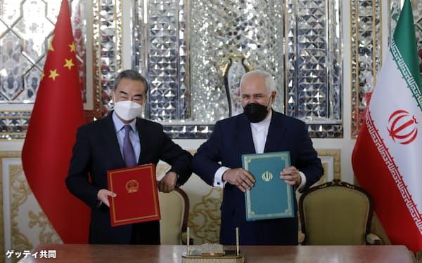 協定に署名した中国の王毅国務委員兼外相(左)とイランのザリフ外相=27日、テヘラン(ゲッティ=共同)