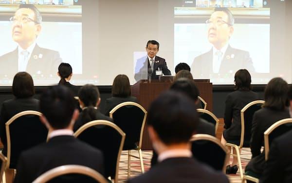 3会場をオンラインでつないだ関西みらいFGの入社式で祝辞を述べる菅社長(1日、大阪市中央区)