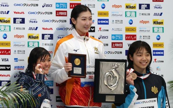 女子100㍍バタフライで優勝しメダルを手にする池江選手(中)
