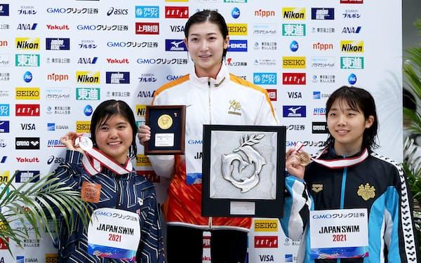 競泳日本選手権の女子100㍍バタフライで優勝し、笑顔を見せる池江璃花子(中)。女子400㍍メドレーリレーの選考基準をクリアして、2大会連続の五輪代表入りを決めた=4日、東京アクアティクスセンター