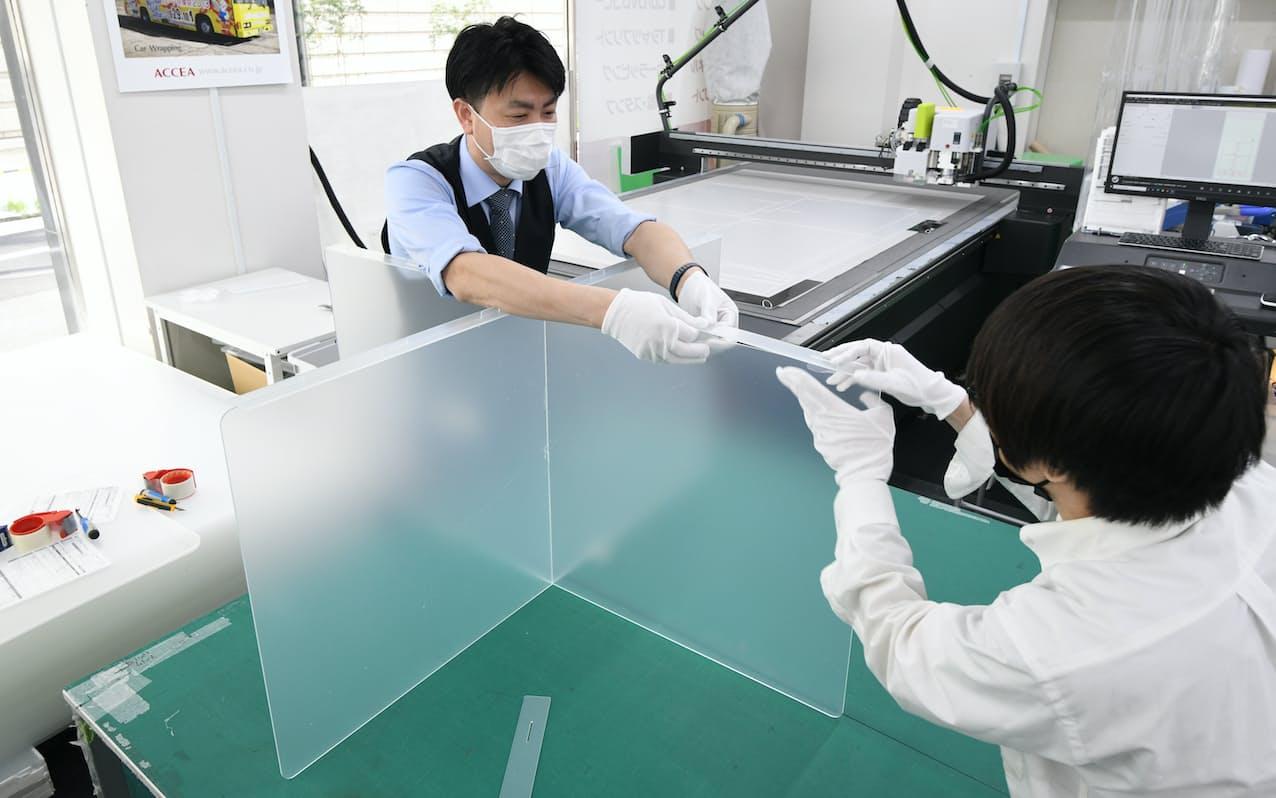客の注文に応じアクリル板をカットし、パーテーションを組み立てるアクセア堂島店の従業員(5日午後、大阪市北区)=目良友樹撮影