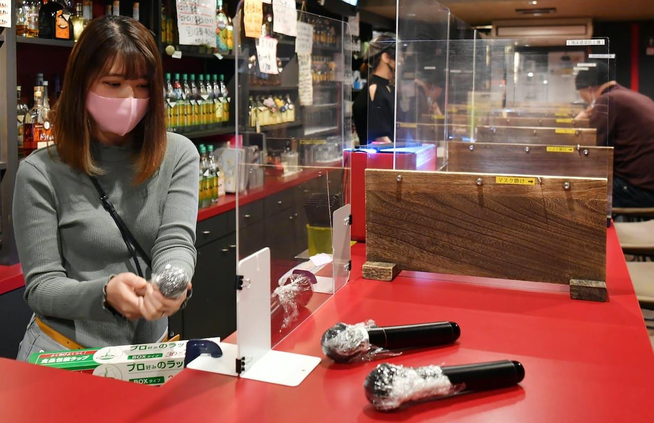 カラオケの利用をやめるカラオケバーでは、店員がマイクを片付けるためラップにくるんでいた(5日午後、大阪市北区)=笹津敏暉撮影
