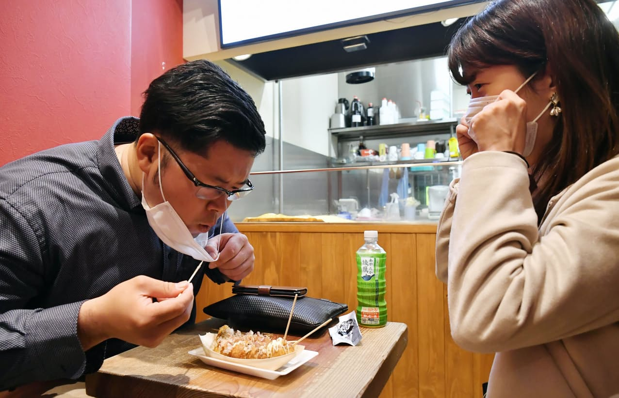 マスクを外してたこ焼きを食べる男性(5日午後、大阪市中央区)=笹津敏暉撮影