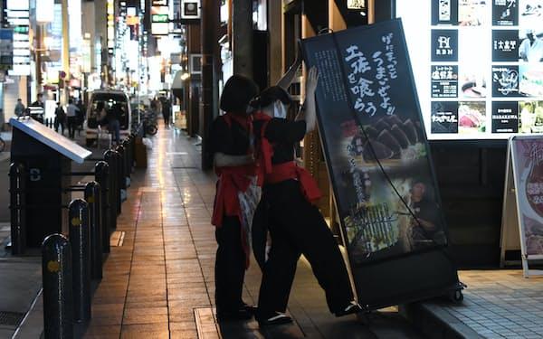 午後7時過ぎ、早くも閉店の準備をする飲食店の店員(5日、大阪市北区)=柏原敬樹撮影