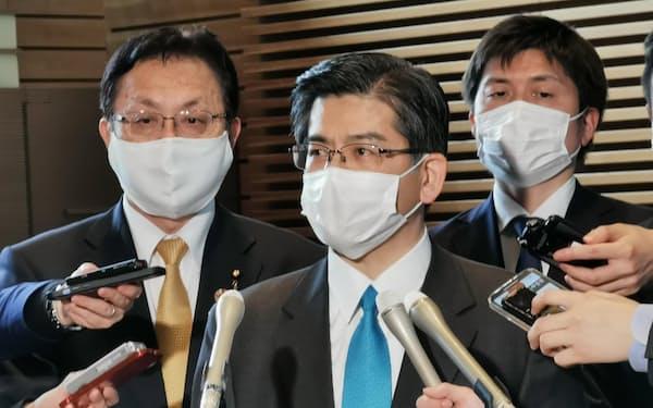記者団の質問に答える公明党の石井啓一幹事長㊥(6日、首相官邸)