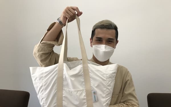 ICチップのタグを付けたエコバッグを掲げる喜多泰之さん