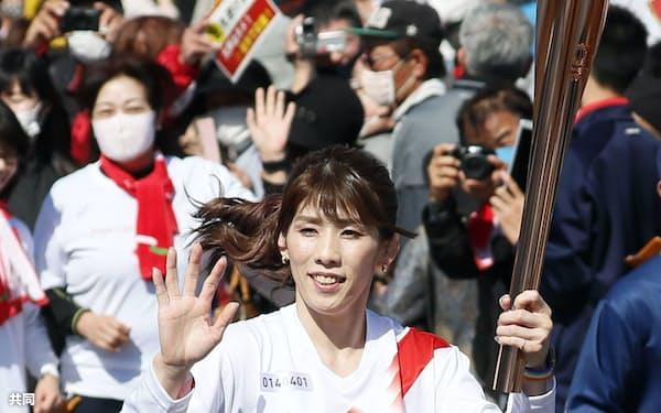 トーチを掲げて故郷の津市を走る聖火ランナーの吉田沙保里さん(7日)=共同