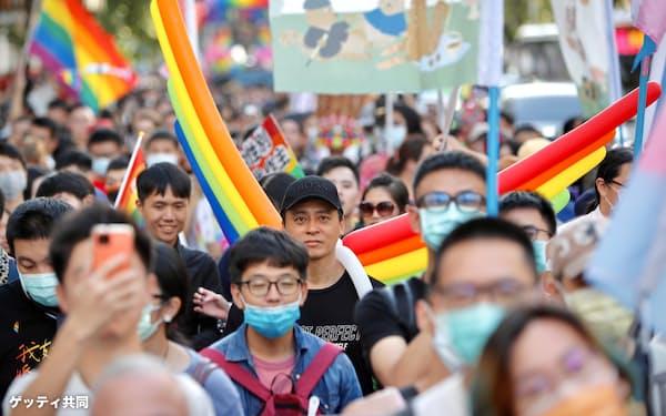 LGBTの権利を訴えるパレードに参加し、虹色の旗を掲げる人たち=2020年10月、台北(ゲッティ=共同)