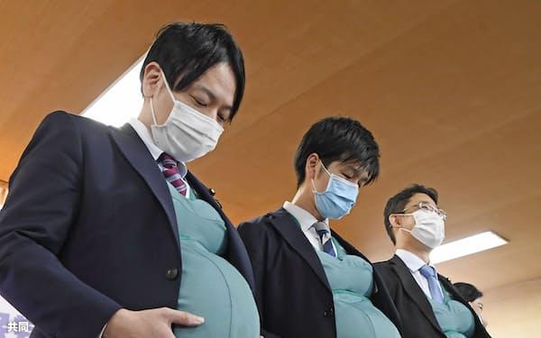 妊婦体験ジャケットを着用した自民党衆院議員の(左から)小倉将信氏、鈴木憲和氏、藤原崇氏(8日午前、東京・永田町の党本部)=共同