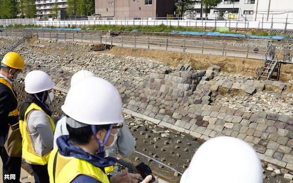 報道陣に公開された「高輪築堤」の信号機跡(中央。9日午前、東京都港区)=共同