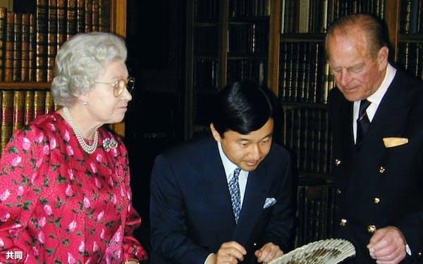 2001年5月、ウィンザー城にある英王室図書館で、皇太子さま(現天皇陛下)に日本皇室ゆかりの所蔵品について説明するエリザベス女王(左)とフィリップ殿下(右)=ロンドン郊外(共同)