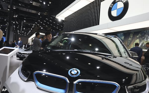FILE - In this Wednesday, April 17, 2019 file photo, a worker cleans an electric vehicle at the BMW booth during the Auto Shanghai 2019 show in Shanghai. Automakers BMW and Volvo announced Wednesday, March 31, 2021 that they support a moratorium on deep sea mining for minerals used in electric vehicle batteries. The call was also backed by Samsung's EV battery unit and tech giant Google. (AP Photo/Ng Han Guan, file)