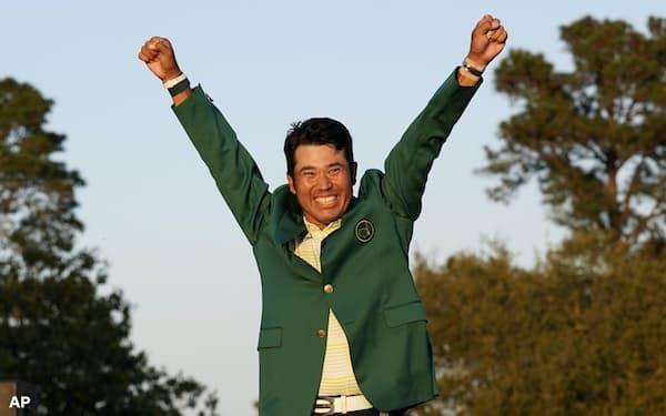 マスターズで優勝し、グリーンジャケットに袖を通し両手を挙げる松山=AP
