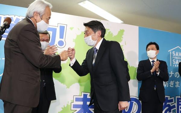 福岡県知事選で当選を決め、笑顔を見せる服部氏(右から2人目)=11日、福岡市