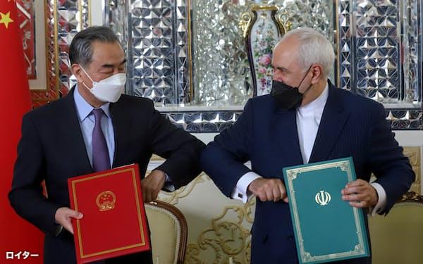 中国の王毅外相(左)とイランのザリフ外相は3月27日に、イランと経済や安全保障を巡る25年間の協定に署名した=ロイター