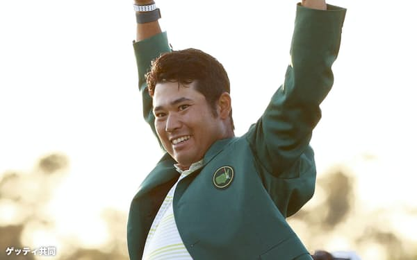 米ゴルフのマスターズ・トーナメントで日本男子初のメジャー制覇を果たし、グリーンジャケットを着て両手を上げる松山=ゲッティ共同