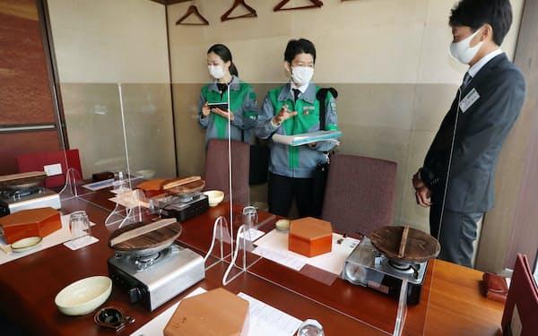 飲食店で客席にアクリル板が設置されているか確認する東京都の職員(12日午後、東京都新宿区)