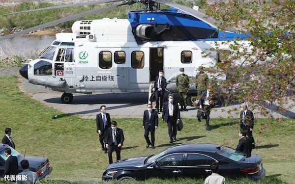 新型コロナウイルスワクチンの集団接種会場視察などのため、陸上自衛隊ヘリコプターで八王子市の市庁舎付近に到着した菅首相(中央)=12日午後、東京都八王子市(代表撮影)