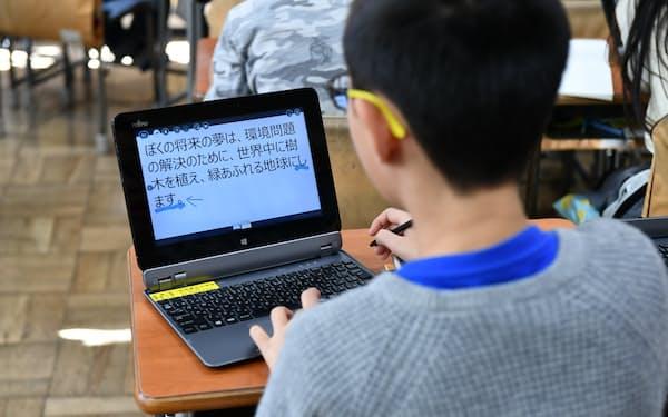 タブレット端末を使い国語の授業を受ける児童(2019年12月、東京都杉並区)