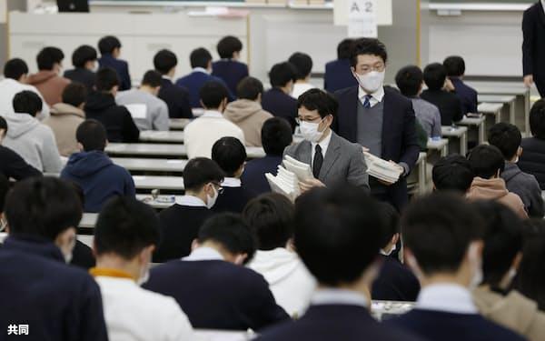 大学入学共通テストの問題用紙を配る試験官(1月、兵庫県西宮市の関西学院大)=共同