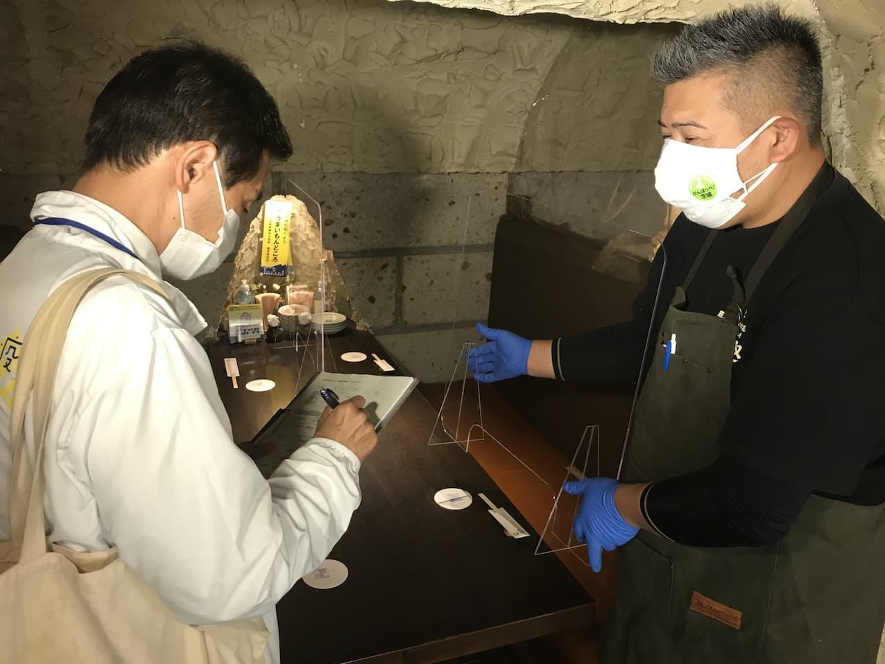14日には酒趣の井坂さん㊨が茨城県職員にパーテーションの設置などを説明した(水戸市)