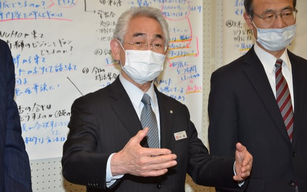 記者団の取材に答える寿都町の片岡春雄町長(写真中央、14日)