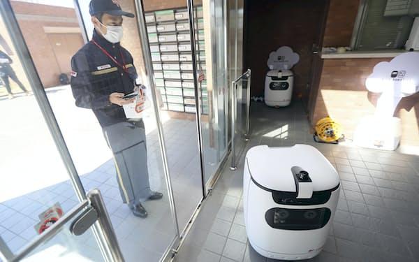 配達員がスマホでロボットを起動する(写真は代表撮影)