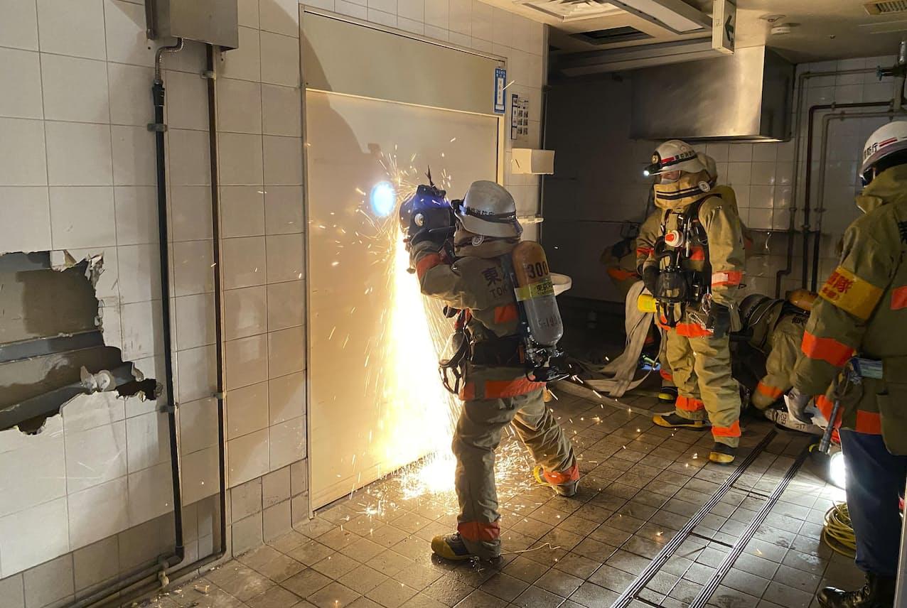 エンジンカッターを使い扉を突き破る訓練をする消防隊員(2020年10月、東京・日本橋)=東京消防庁提供・共同