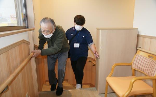 階段の上り下りのリハビリで施設利用者に付き添う理学療法士㊨(高知市内のケセラ介良)