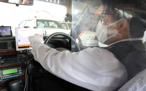 「おでかけ号」車内のタブレット端末で最適ルートを受信した運転手(13日、栃木県下野市)