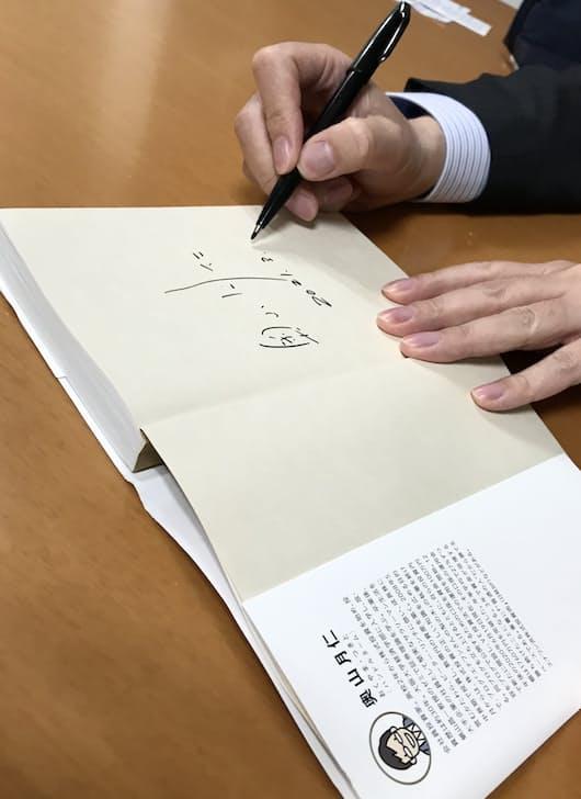 ろくすけさんが今回の対談に奥山さんの著書を持参。それにサインを記す奥山さん