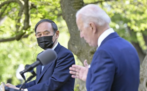 会談後、共同記者会見でバイデン米大統領(右)の発言を聞く菅首相=16日、ワシントンのホワイトハウス(共同)