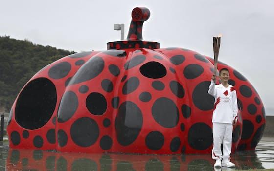 芸術家草間弥生さんの代表的な作品「赤かぼちゃ」の前に到着した聖火ランナー(17日、香川県直島町)=共同