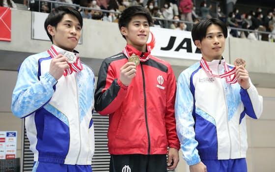 全日本体操個人総合選手権の男子決勝、メダルを手に笑顔を見せる優勝した橋本大輝(中央)、2位の谷川航(左)、3位の萱和磨(18日、群馬・高崎アリーナ)=代表撮影