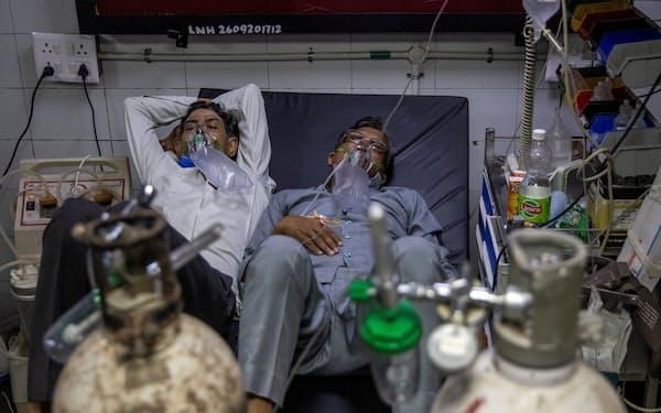 インドの首都ニューデリーでは病床不足のため酸素マスクを着けた患者2人が1つのベッドに横たわる=ロイター