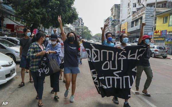 19日、最大都市ヤンゴンで国軍への抗議を続ける若者たち=AP