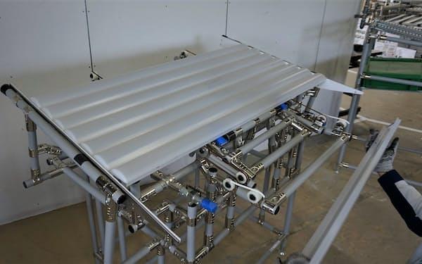 パナソニック新潟工場の「からくりインバータ」。LEDベースライトの自動組み立て機に、細長い白色のカバー部品を供給する。モーターや圧縮エアーといった独自の動力を必要としない(出所:日経クロステック)