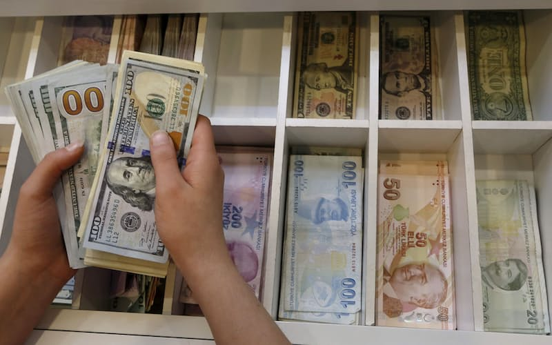 FILE PHOTO: A money changer counts U.S. dollar bills, with Turkish lira banknotes in the background, at an currency exchange office in central Istanbul, Turkey, August 21, 2015. REUTERS/Murad Sezer/File Photo