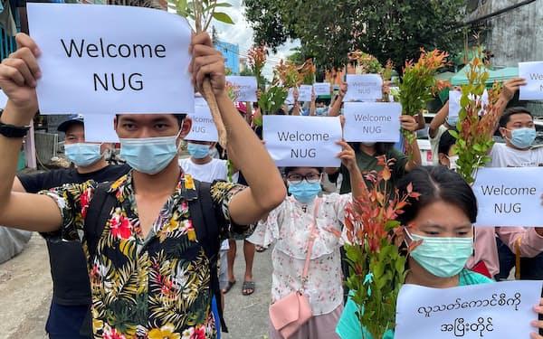民主派が設立した「挙国一致内閣」への支持を表明してデモ行進する人々(17日、ヤンゴン)=ロイター